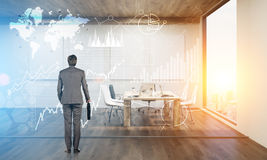 Vue arrière d'un homme regardant des hologrammes sur le mur de salle de conférence Images stock