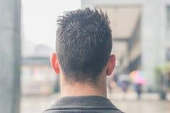 Vue arrière d'un jeune homme posant dans les rues de ville Photographie stock libre de droits