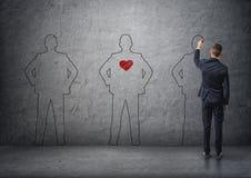 Vue arrière d'un men& x27 de dessin d'homme d'affaires ; silhouettes de s sur le mur en béton Le moyen avec le coeur rouge dans s Images stock