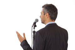 Vue arrière d'un orateur parlant au microphone Image stock