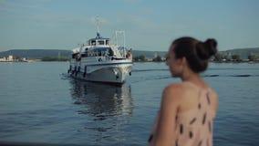 Vue arrière d'une belle fille observant un bateau de croisière approcher le pilier banque de vidéos
