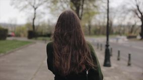 Vue arrière d'une belle jeune fille avec de longs cheveux bruns ayant une promenade au printemps Mouvement lent clips vidéos