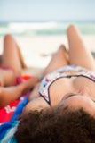 Vue arrière d'une femme attirante se trouvant sur un essuie-main de plage dans l'avant Photo stock