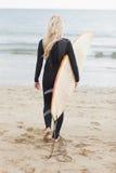 Vue arrière d'une femme dans le vêtement isothermique tenant la planche de surf à la plage Photos stock