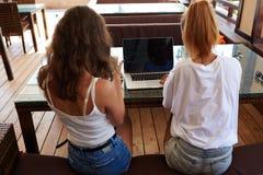 Vue arrière d'une femme qui travaillant sur l'ordinateur portable avec l'écran vide de l'espace de copie tandis que ses amis caus Images stock