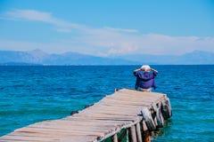 Vue arrière d'une femme s'asseyant sur une jetée en bois minuscule par la mer Jeune belle fille s'asseyant sur la jetée Vue arriè image libre de droits