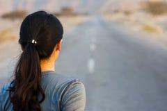 Vue arrière d'une fille courant sur la route Photo stock