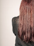 Vue arrière d'une jeune femme avec de longs cheveux bruns contre le copyspace gris de fond Photographie stock