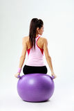 Vue arrière d'une jeune femme de sport s'asseyant sur le fitball avec des dumbells image stock