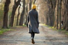 Vue arri?re d'une jeune femme marchant sur une avenue photographie stock libre de droits