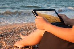 Vue arrière d'une jeune fille vers son comprimé avec la photo d'amour sur la plage Images stock