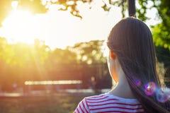 Vue arrière d'une jolie fille avec de longs cheveux bruns lisant un livre en parc dans le coucher du soleil Images libres de droits