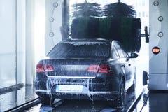 Vue arrière d'une lave-auto nettoyant une voiture avec les brosses tournantes photo libre de droits