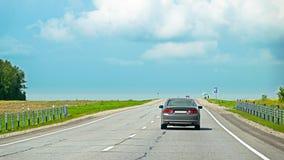 Vue arrière d'une voiture expédiant sur la route goudronnée dans la campagne Photo libre de droits