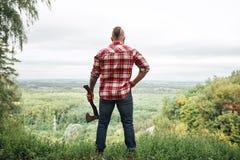Vue arrière de bûcheron dans la forêt tenant une hache sur son épaule photo libre de droits