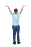 Vue arrière de bel homme dans des jeans regardant le mur et les prises h Image libre de droits