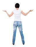 Vue arrière de belle femme dans des jeans regardant le mur et les prises Photos stock