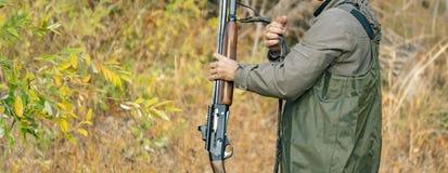 Vue arrière de chasseur porter le shotgu classique de fusil dans la forêt f images stock