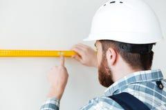 Vue arrière de constructeur de l'homme utilisant la règle pour mesurer la longueur Image stock