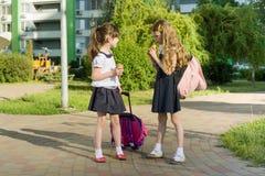 Vue arrière de deux amies d'écolière avec des sacs à dos mangeant la crème glacée  Photos stock