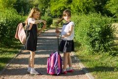 Vue arrière de deux amies d'écolière avec des sacs à dos mangeant la crème glacée  Photo stock