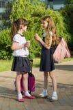 Vue arrière de deux amies d'écolière avec des sacs à dos mangeant la crème glacée  Image stock