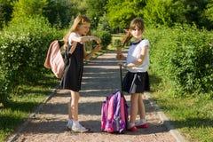 Vue arrière de deux amies d'écolière avec des sacs à dos mangeant la crème glacée  Photographie stock