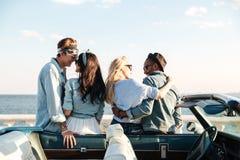 Vue arrière de deux couples embrassant près du cabriolet Photo libre de droits