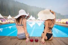Vue arrière de deux femmes dans des chapeaux se reposant au bord de la piscine avec des cocktails sur le fond des forêts Images libres de droits