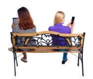 Vue arrière de deux femmes s'asseyant sur le banc et les regards à l'écran le comprimé Image stock
