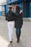 Vue arrière de deux filles de embrassement sur une rue Photographie stock libre de droits
