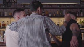 Vue arrière de deux hommes s'asseyant au compteur de barre Troisième type joignant la société, étreindre de compagnons Amis mascu clips vidéos