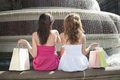 Vue arrière de deux jeunes amis féminins avec des paniers se reposant par la fontaine d'eau Photos libres de droits