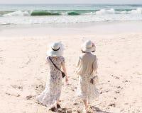 Vue arrière de deux jeunes femmes dans de longs robes et chapeaux marchant le long de la plage sablonneuse images libres de droits