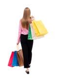 Vue arrière de femme allante avec des sacs à provisions Image libre de droits