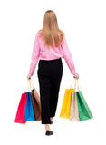Vue arrière de femme allante avec des sacs à provisions Photos libres de droits