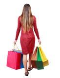 Vue arrière de femme allante avec des sacs à provisions Photos stock