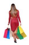 Vue arrière de femme allante avec des sacs à provisions Image stock