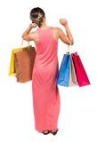 Vue arrière de femme allante dans la femme de robe avec des sacs à provisions Image stock