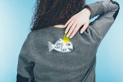 vue arrière de femme avec de poissons le dos tiré par la main dessus, concept de jour d'imbéciles d'avril photos libres de droits