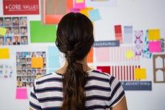 Vue arrière de femme d'affaires contre les notes collantes dans le bureau Images stock