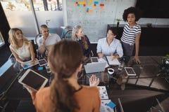 Vue arrière de femme d'affaires expliquant des stratégies aux collègues dans le bureau Images stock