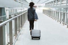 Vue arrière de femme d'affaires marchant avec la valise Photos stock