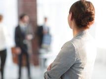 Vue arrière de femme d'affaires sur le bureau brouillé de fond Image libre de droits