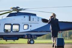 Vue arrière de femme d'affaires Walking Towards Helicopter tandis que Tal Image stock