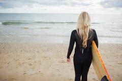 Vue arrière de femme dans le vêtement isothermique avec la planche de surf à la plage Images stock