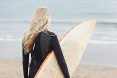 Vue arrière de femme dans le vêtement isothermique tenant la planche de surf à la plage Photo libre de droits