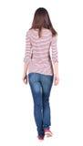 Vue arrière de femme de marche dans des jeans Image stock