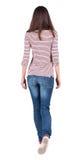 Vue arrière de femme de marche dans des jeans Photo libre de droits