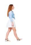 Vue arrière de femme de marche dans la robe belle fille rousse dedans Image libre de droits